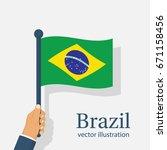 brazil flag holding in hand.... | Shutterstock .eps vector #671158456