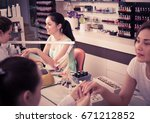 Small photo of pair of women clients getting manicure in modern nail salon