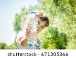 baby drinks water from bottle. | Shutterstock . vector #671305366