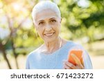 joyful senior woman listening... | Shutterstock . vector #671423272