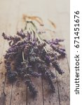 Small photo of Bundle of lavender on a rough wood. Soft and defocused image. Vintage image. Dark image because of the moody tones.