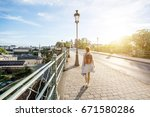 woman walking on the bridge... | Shutterstock . vector #671580286