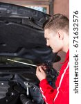 Small photo of Young male motor mechanic checking the oil level in a car engine holding the dipstick over the open engine compartment