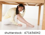 young woman hiding under table... | Shutterstock . vector #671656042