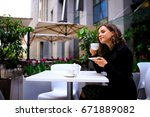 beautiful girl in a cafe amidst ... | Shutterstock . vector #671889082
