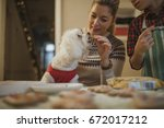 Stock photo mature woman is baking christmas biscuits with her son her pet dog is sitting on her knee and she 672017212