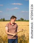 Small photo of Young agronomist in wheat field, harvest, grain quality