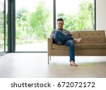 young happy man on sofa using... | Shutterstock . vector #672072172