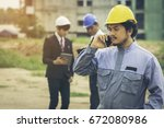 Small photo of Young engineers with the beard, wear helmets using smartphones to liaise with contractors in the construction of large building. There are two people standing liaison engineer behind them.