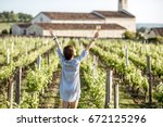 Stock photo young woman with glass of wine enjoying beautiful sunset view on the vineyard in bordeaux region in 672125296