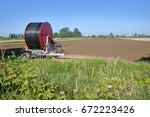 Small photo of A large irrigation wheel and hose is used to water acres of prime farm land during the dry summer months.