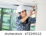 female cctv installer... | Shutterstock . vector #672240112