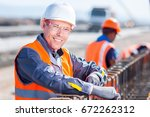 worker fixing steel rebar at... | Shutterstock . vector #672262312