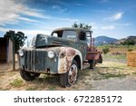 rusted old truck near a farm | Shutterstock . vector #672285172