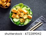fried tofu salad with cucumbers ... | Shutterstock . vector #672289042
