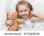 girl holding her brown teddy ... | Shutterstock . vector #672369025