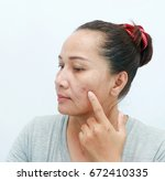 Small photo of woman is agape mortified about spot in the skin.