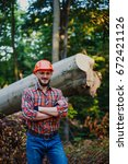Small photo of Portrait of a young successful happy logger against a background of a large cut tree