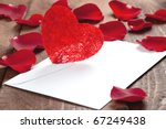 envelope with heart and rose petals - stock photo