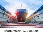 ship in floating dry dock under repair by sandblasting and painting in shipyard