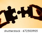 hands holding puzzle pieces ... | Shutterstock . vector #672503905