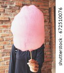 woman eating cotton candy on... | Shutterstock . vector #672510076