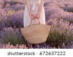 Stock photo woman holding wicker bag in her hands in pink dress 672637222