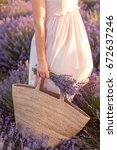 Stock photo pretty woman holding wicker bag and lavender bouquet in her hand and dancing 672637246
