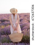 Stock photo woman holding wicker bag in her hands wearing fedora hat on sunset in lavender field 672637306