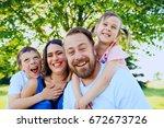 portrait of happy parents... | Shutterstock . vector #672673726
