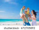 young family of four on beach... | Shutterstock . vector #672705892