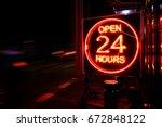 open 24 hours neon sign on the... | Shutterstock . vector #672848122