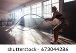 woman lifting heavy weights at... | Shutterstock . vector #673044286