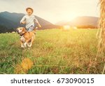 Stock photo boy and dog run together on the field with haystacks 673090015