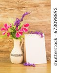 Small photo of Mocap, background from a blank white sheet of paper in a notebook near bright plastic walls and ceramic vase with pink and purple garden flowers on wooden table, vertical, mock up