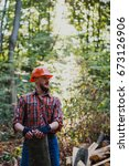 Small photo of Portrait of a logger in a helmet with a log