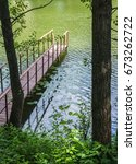 Small photo of wooden gangway with railings on the lake