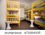 Stock photo interior of the hostel bedroom hostel with wooden bunk beds 673304335