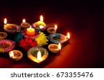colorful clay diya lamps lit... | Shutterstock . vector #673355476