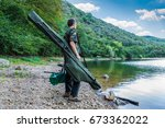Small photo of Fishing adventures, carp fishing. Fisherman on a lake shore with camouflage fishing gear, green bag and rod holdall