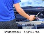 the hand of an auto mechanic... | Shutterstock . vector #673483756