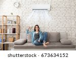 Small photo of Happy Young Woman Holding Remote Control Relaxing Under The Air Conditioner