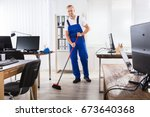 smiling male janitor cleaning... | Shutterstock . vector #673640368