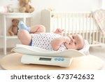 baby lying on scales in room | Shutterstock . vector #673742632