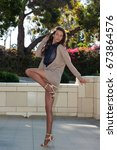 Small photo of Pretty brunette in tan pantyhose and sweater and open toe heels taking a high step.