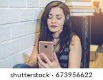 woman in headphones listening...   Shutterstock . vector #673956622