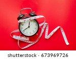 black alarm clock and measuring ... | Shutterstock . vector #673969726