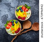Small photo of Green Smoothie in bowls for healthy breakfast. Fresh organic smoothie made from spinach, banana, spirulina,wheatgrass and lime with berries and fruits on black background.Top view, copy space
