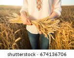 Small photo of the woman in a national white shirt holding the golden ripened wheat sheaf on background of meadow wheat field. harvest, agriculture, agronomics, food, production, eco concept.