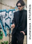 Small photo of White caucasian handsome bearded man in black suit and stylish glasses smoking cigarette on the street. Vintage effect. Clothes advertising campaign concept.